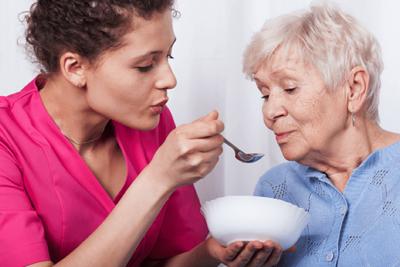 Caregiver feeding an elderly woman