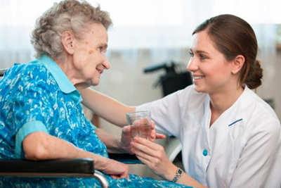 Nurse giving water to an elderly woman sitting down