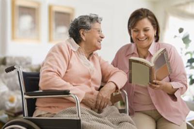 Care giver reading a book to a senior citizen